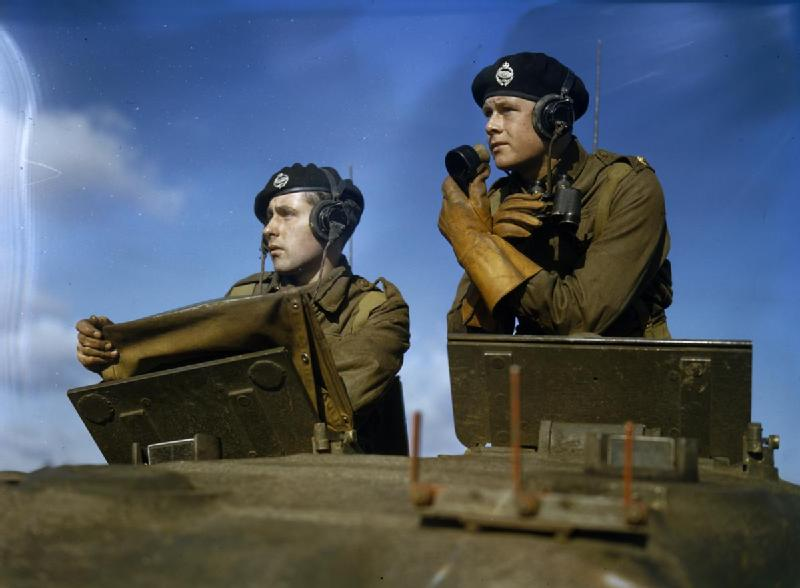 Squadron leader in the turret of a Churchill tank giving orders through a microphone; IWM TR 218